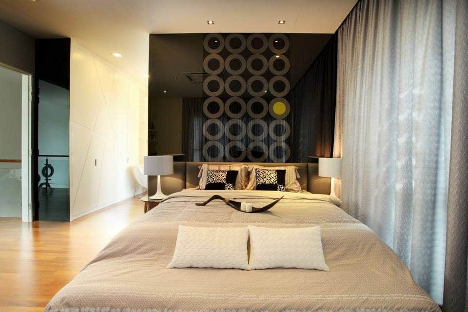 Mirrored wall above headboard with geometric pattern for this condominium in Puchong
