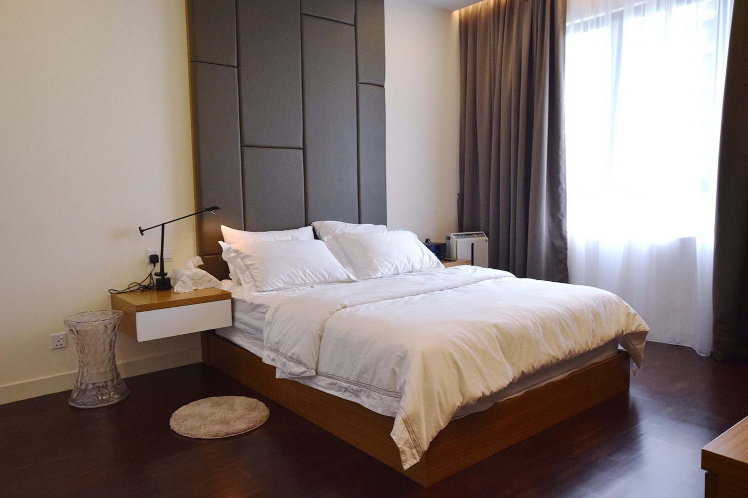 Floating bedside tables and dark wood flooring for this condominium in Windows On The Park, KL