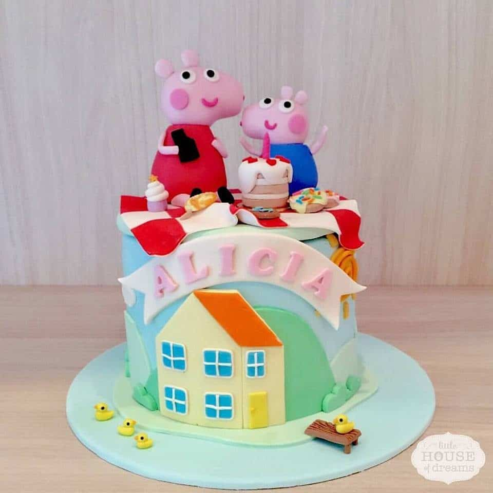 A round cake decorated with edible Peppa and George figurines. Little House of Dreams.Source