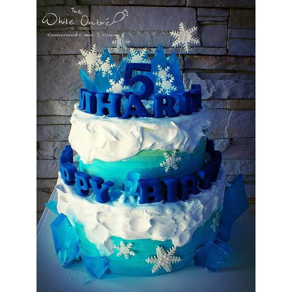 A two-tiered round cake gorgeously decorated with edible sugar rocks, snowflakes and for a Frozen themed cake. The White Ombre.Source