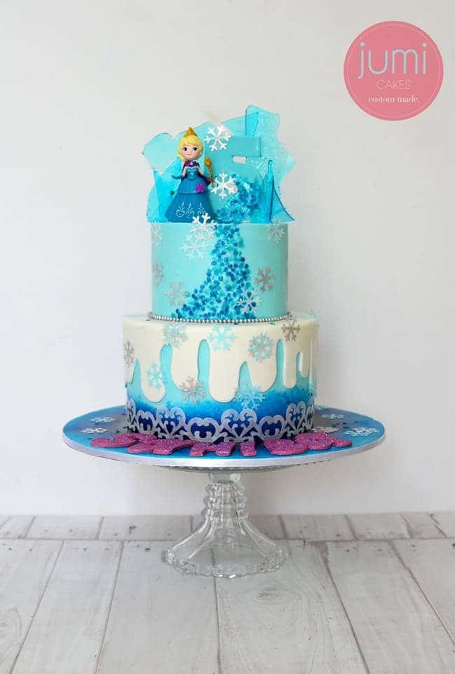 A two-tiered Frozen themed cake that was decorated with edible paint, fondant and sugar glass detailings. Jumi Cakes.Source