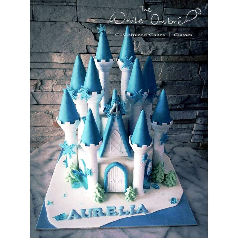 a multi tiered cake with decoration made of fondant that resemble the ice castle from