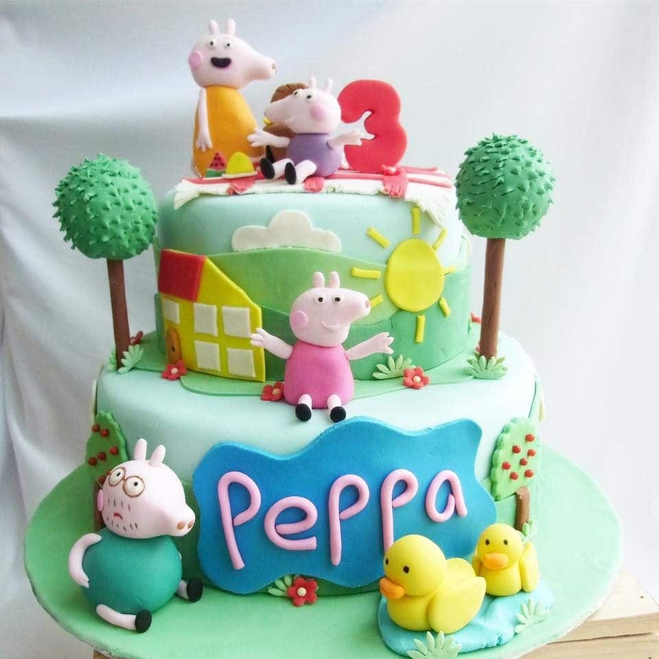 A two-tiered fondant cake with edible figurines of Peppa, George, Mummy and Daddy Pig, and fondant cutouts to fully decorate the cake.  Corine and Cake.Source