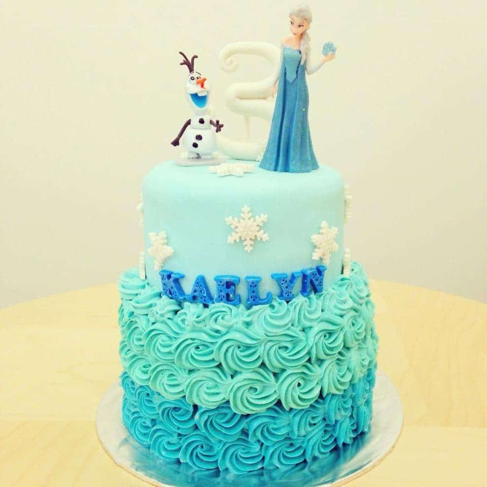A two-tiered Frozen themed cake decorated with buttercream and fondant. Little House of Dreams. Source