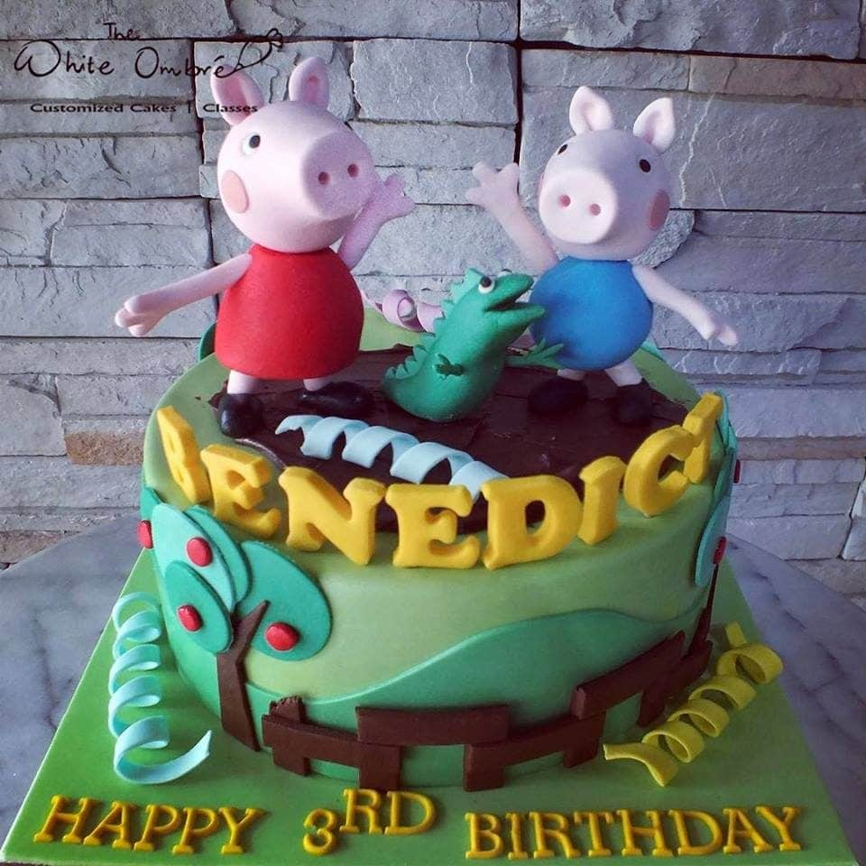 Edible figurines of Peppa, George and Dinosaur (George's favourite toy) playing on a (chocolate ganache) muddy puddle. The White Ombre.Source