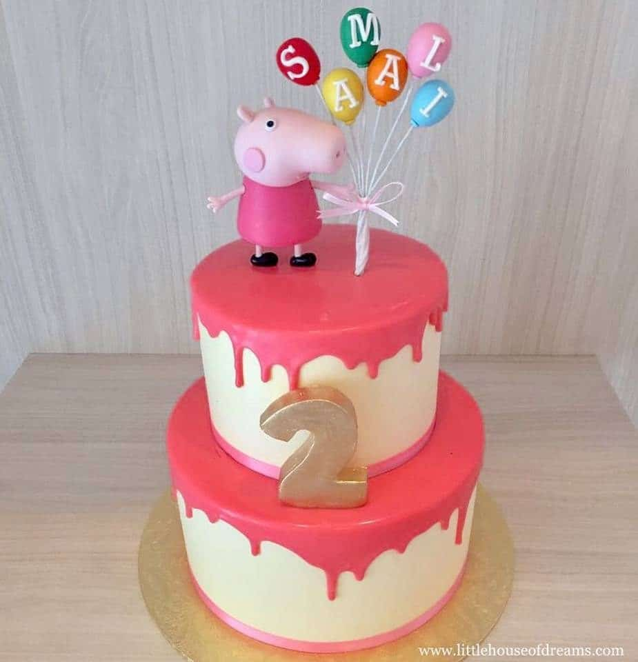A two-tiered cake with dripping frosting effect and Peppa Pig figurine cake topper. Little House of Dreams.Source