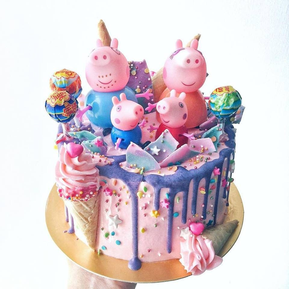 A Peppa Pig themed cake with rainbow coloured frosting, lollipops and figurines. Corine and Cake.Source