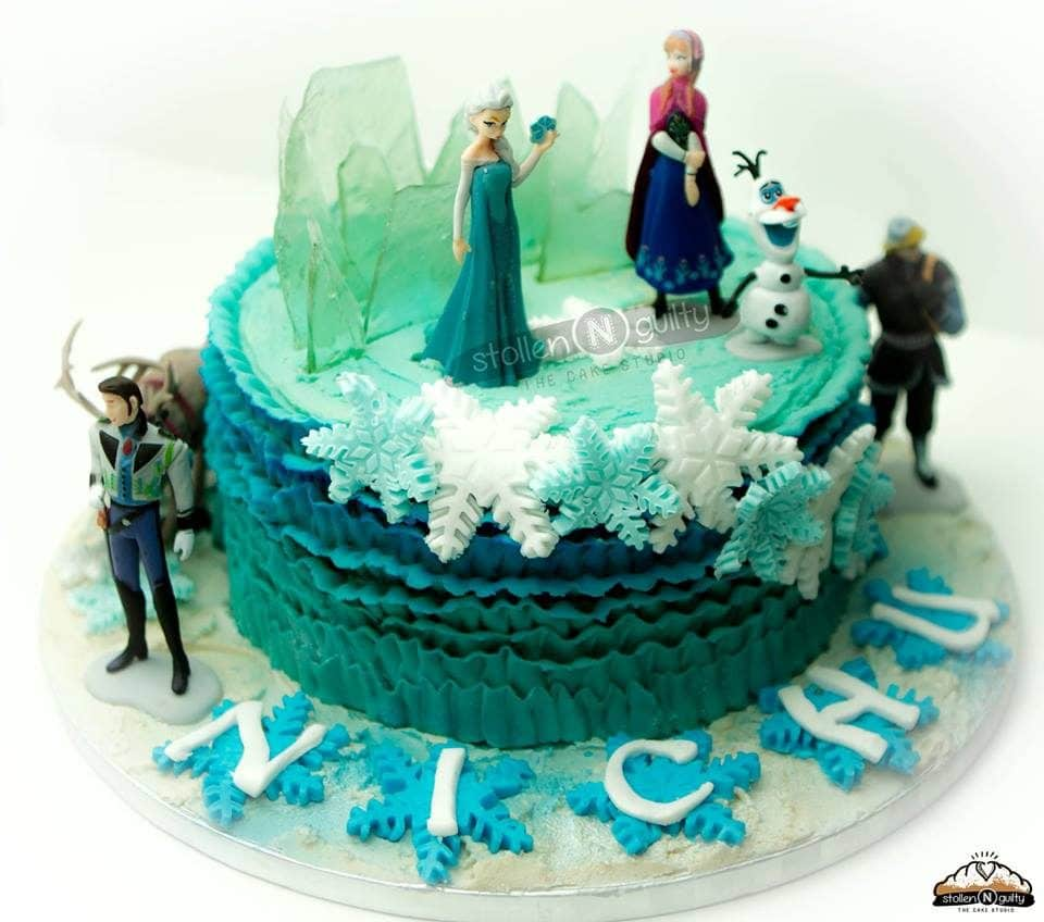 A round cake decorated with buttercream frosting, edible sugar glass and snowflakes, and figurines of all the main characters from Frozen. Stollen N Guilty. Source