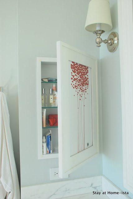 Recessed cosmetics cabinet hidden behind artwork
