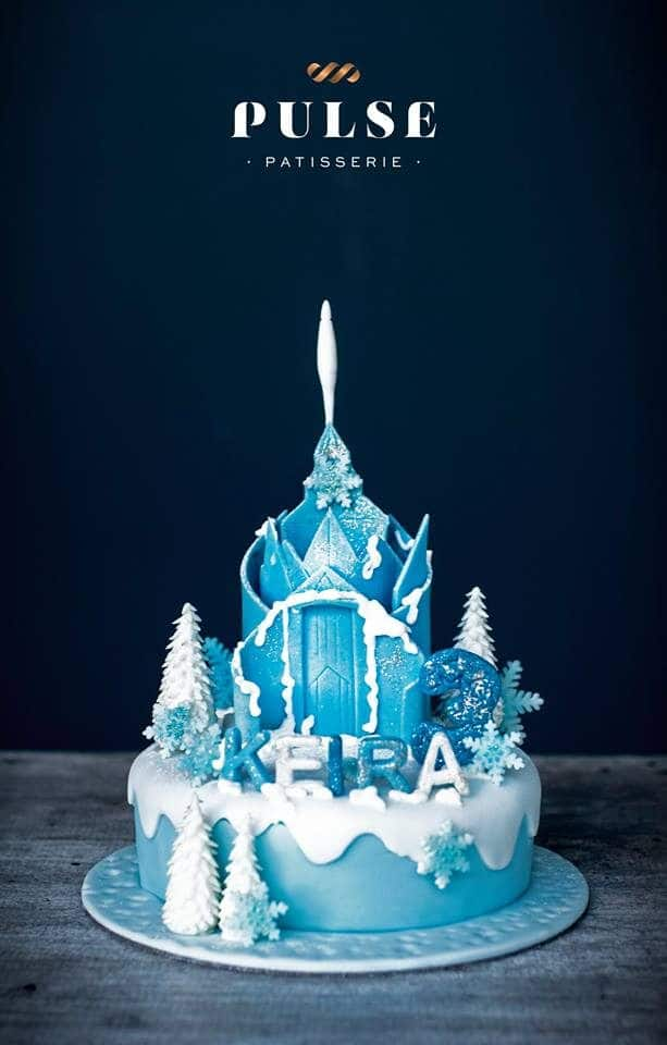 Queen Elsa's Ice Castle cake made of blue and white fondant. Made by: Pulse Patisserie. Source