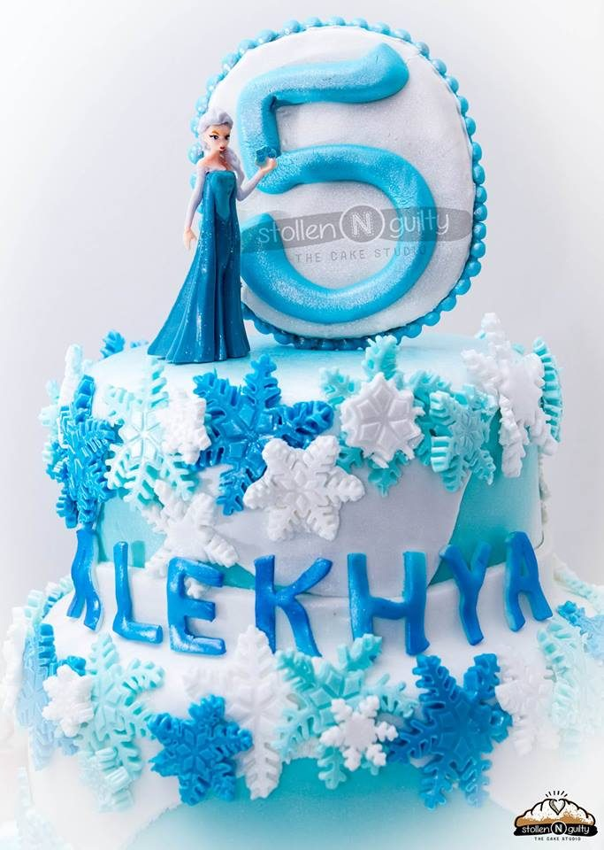 A regular two-tiered round cake decorated with white and blue fondant to create a Frozen themed cake. Stollen N Guilty .Source