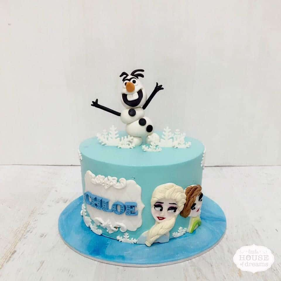 A Frozen themed round cake with edible Olaf figurine cake topper, 2D image of Elsa and Anna. Little House of Dreams.Source