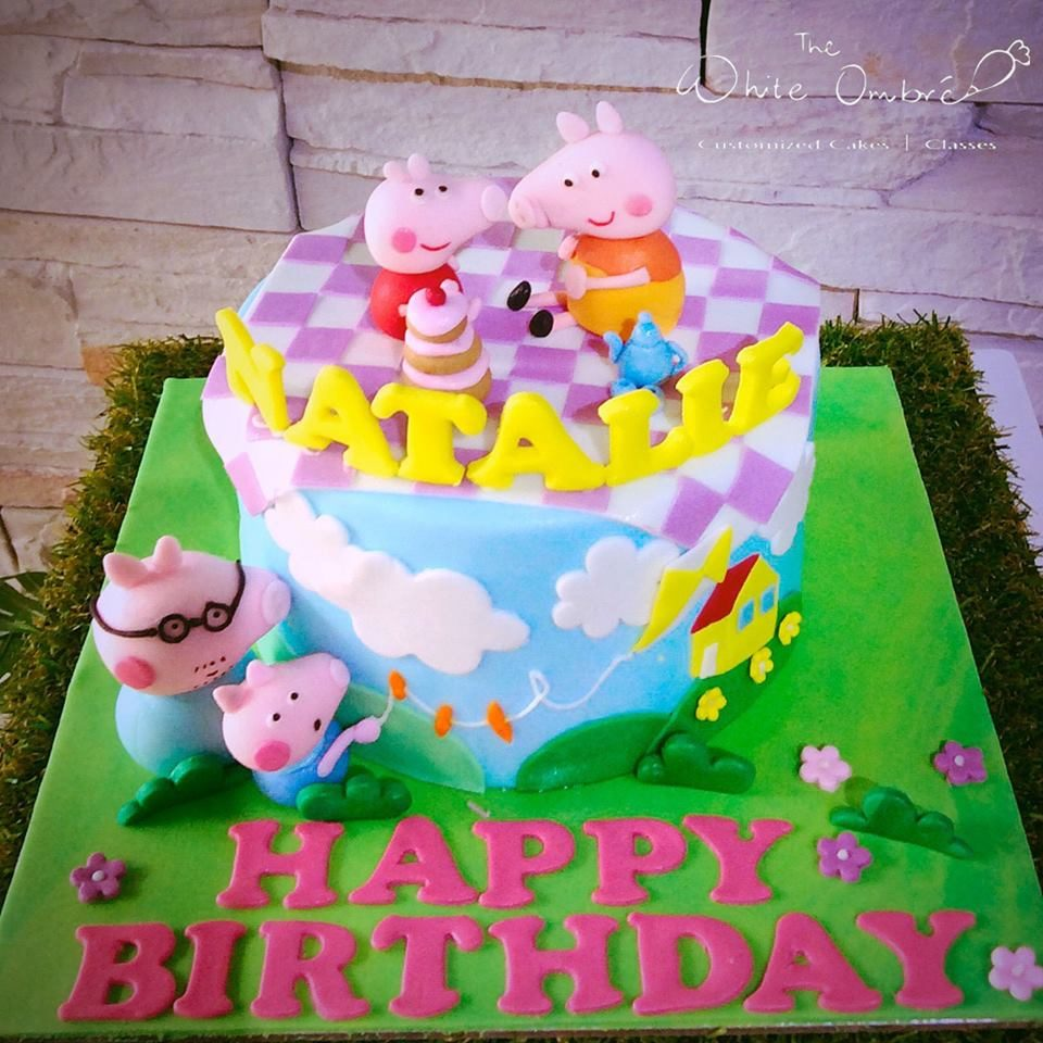 A round cake with fondant decorations and edible figurines of Peppa, George, Mummy and Daddy Pig. The White Ombre.Source
