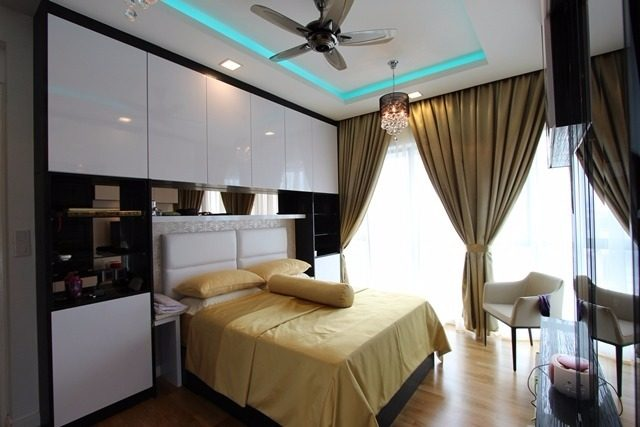 In this bedroom in Setia Sky by Ark Studio, ceiling-height storage is built around the head of the bed. Floating drawers were also added on the opposite wall deep enough for a TV.