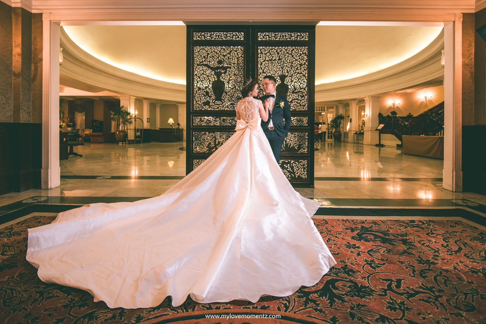 Bride and groom posing outside the ballroom of the E&O Hotel in Penang, Malaysia. Photo by My Love Momentz