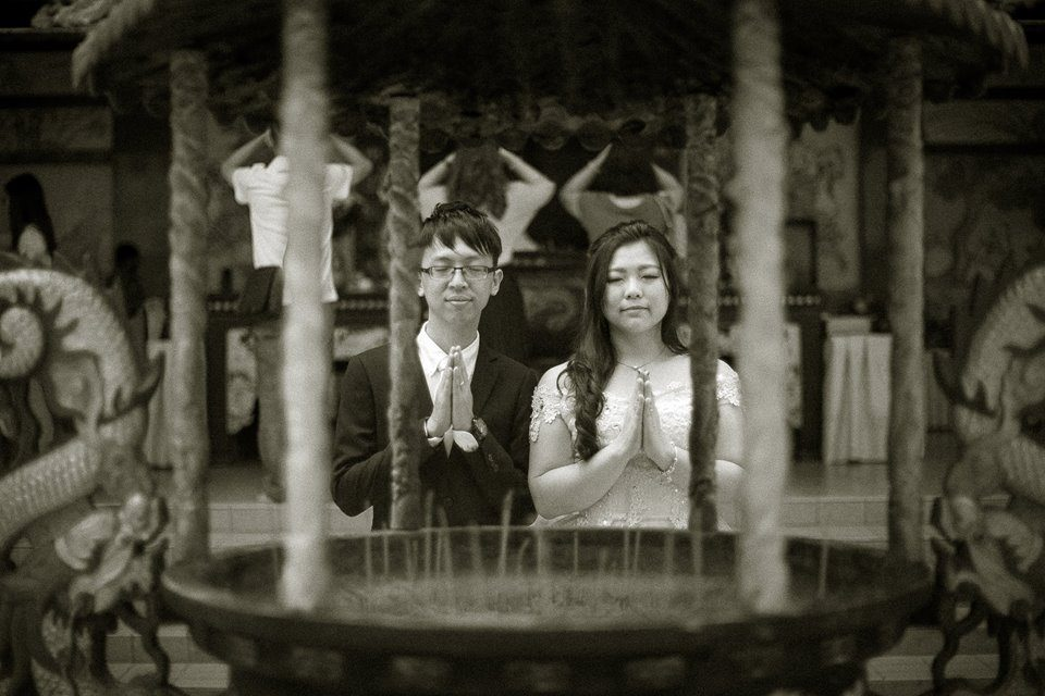 Wedding couple prays for blessings at Thean Hou Temple Kuala Lumpur. Photo by J Seven Studios. Hire wedding photographers at Recommend.my