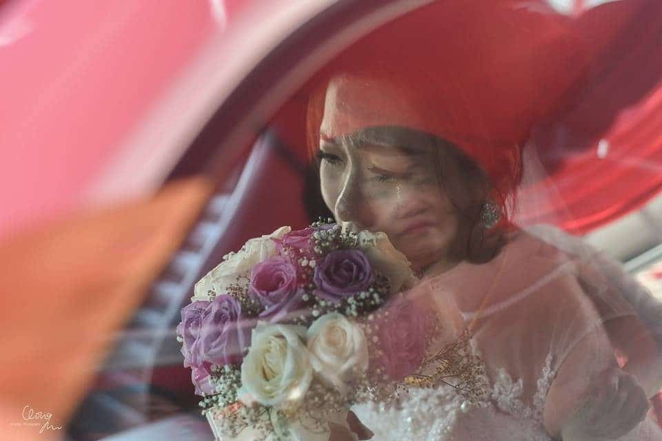 Bride tearing up as she leaves her parents' home in Malaysia, as mother's face is reflected in the car window. Photo by Qinghui Photography. Wedding photographers in Malaysia at Recommend.my