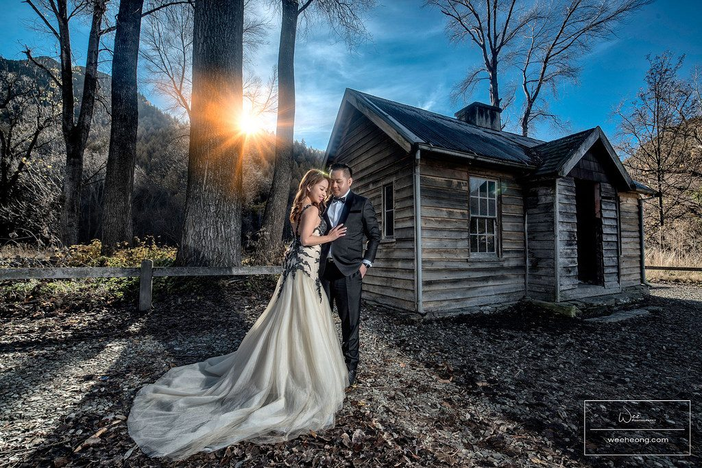 Malaysian wedding couple poses for prewedding photograph by a wooden hut in New Zealand. Photo by Wee Heong Photography