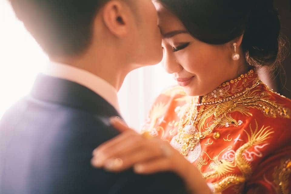 Groom kisses bride on the forehead before Malaysian Chinese wedding tea ceremony. Photo by Shuttering Hearts
