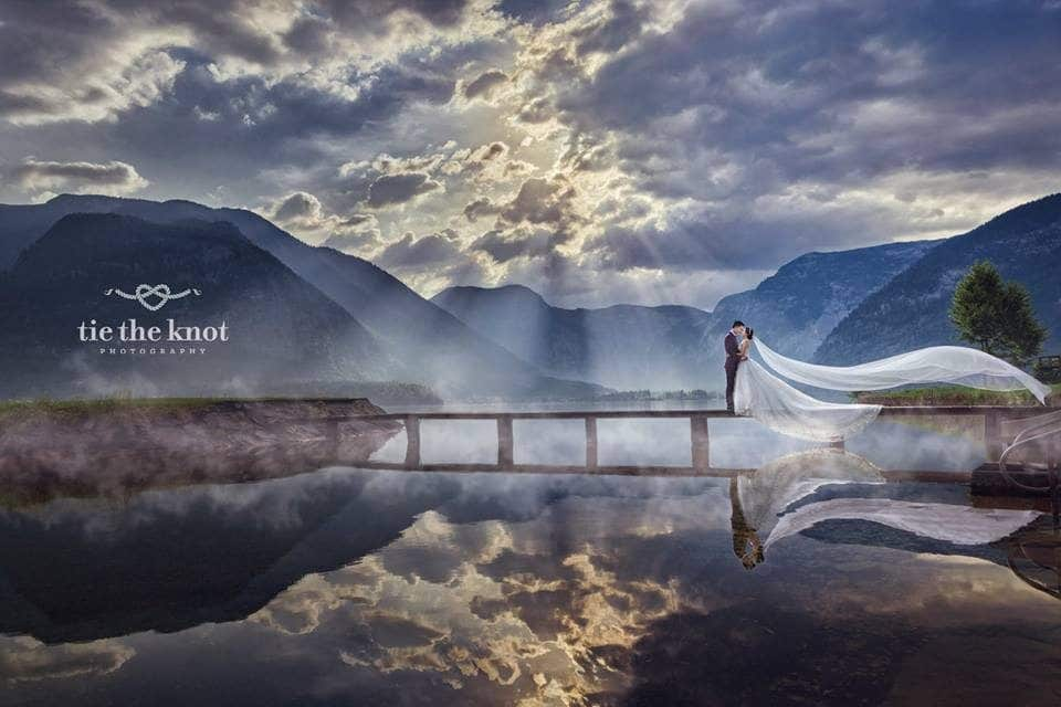 Pre-wedding photograph of couple on a footbridge across a lake in Halstatt Austria. By Tie The Knot Photography. Get quotes for your destination wedding at Recommend.my