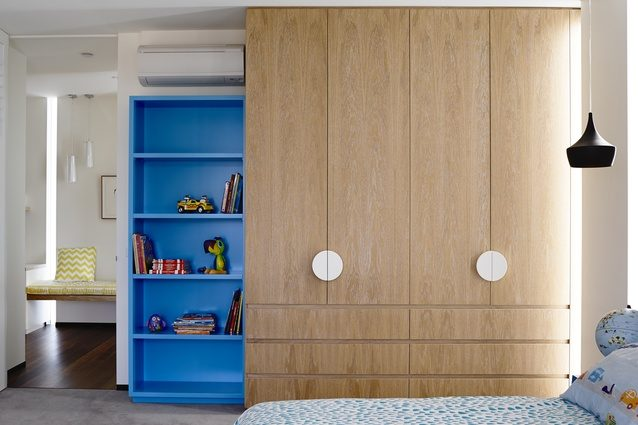Natural timber kids cupboard with bright blue display shelves