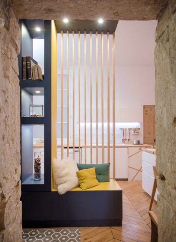 Bright yellow partition with wooden slats and seating