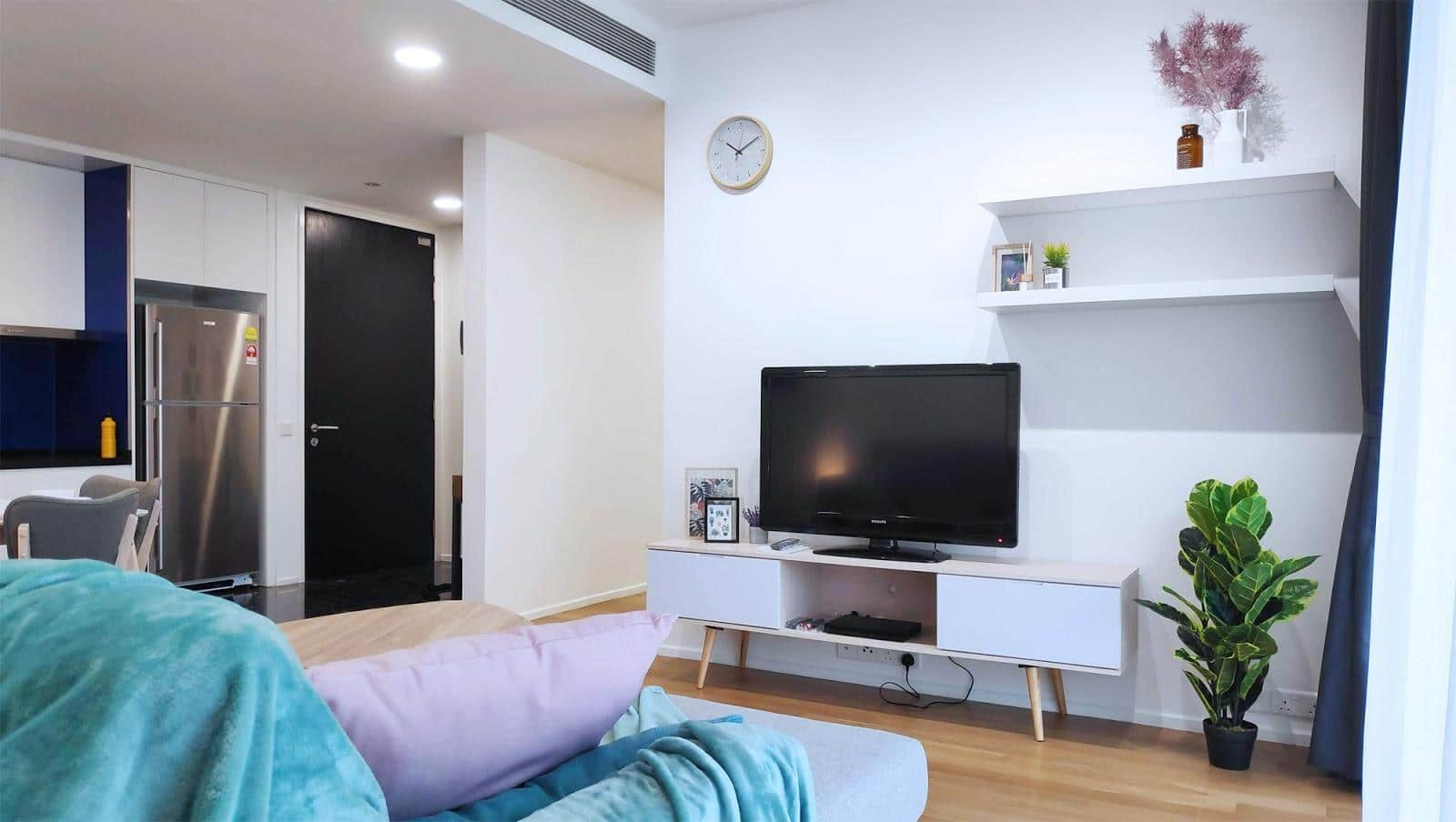 Konsol TV di ruang tamu, dengan dua rak putih terpasang di sudut kanan atas