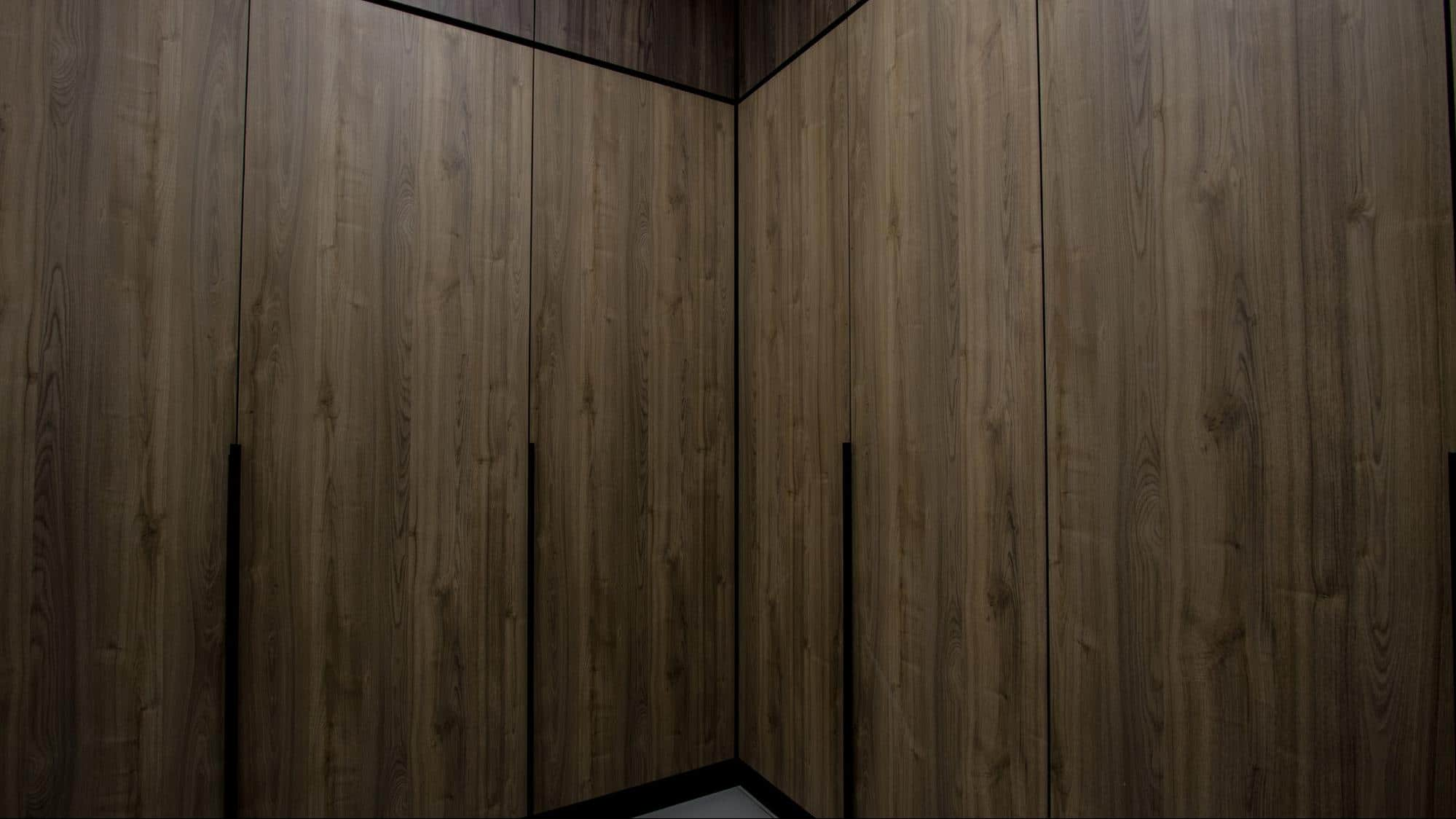 Walk-in wardrobe with brown built-in cabinetry