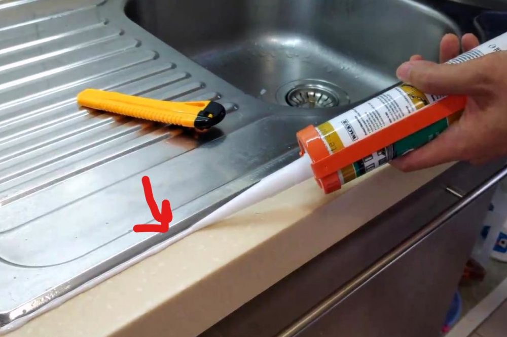 Applying the sealant around the edge of the sink
