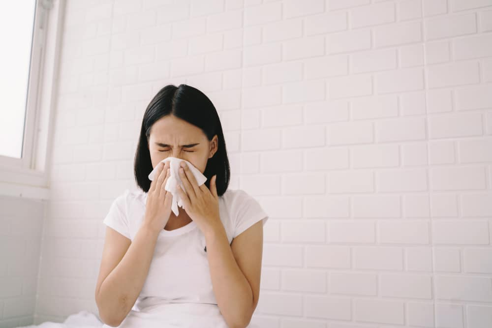 Woman sneezing due to allergies from dusty curtains