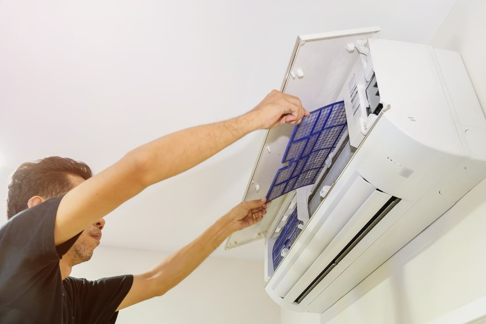 Clogged aircon filter being removed for cleaning